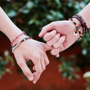 zwei Menschen die sich an den Händen halten